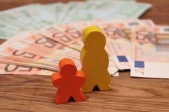 Família de madeira com dinheiro imagem de stock