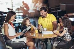 Família de quatro membros que tem o grande tempo em um restaurante imagens de stock