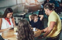 Família de quatro membros que tem o grande tempo em um restaurante fotos de stock