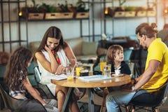 Família de quatro membros que tem o grande tempo em um restaurante foto de stock royalty free