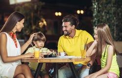 Família de quatro membros que tem o grande tempo em um restaurante foto de stock
