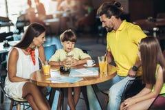 Família de quatro membros que tem o grande tempo em um restaurante imagem de stock