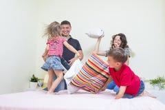 Família de quatro pessoas caucasiano nova que tem uma luta de descanso engraçada brincalhão na cama dentro Imagens de Stock