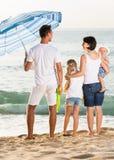 Família de quatro pessoas contente que está com dianteiro traseiro Imagens de Stock Royalty Free