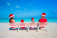Família de quatro pessoas feliz em Santa Hat no verão Imagem de Stock