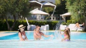 Família de quatro pessoas feliz na piscina do ar livre filme