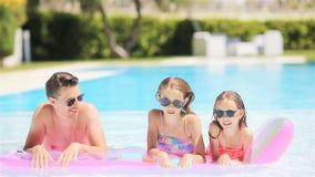 Família de quatro pessoas feliz na piscina do ar livre video estoque