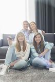Família de quatro pessoas feliz que olha a tevê junto em casa Fotografia de Stock Royalty Free