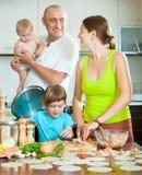 A família de quatro pessoas junto na cozinha prepara o opetitnuyu do alimento Fotografia de Stock