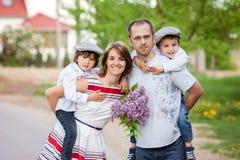 Família de quatro pessoas, mãe, pai e dois meninos, pai que tem o k imagem de stock royalty free