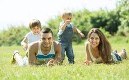 Família de quatro pessoas na grama no parque Imagem de Stock