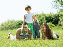 Família de quatro pessoas na grama no parque Foto de Stock