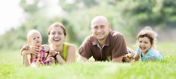 Família de quatro pessoas na grama verde Foto de Stock Royalty Free