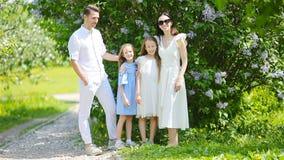 Família de quatro pessoas no jardim de florescência no dia de mola bonito video estoque