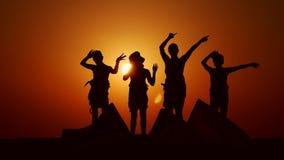 Família de quatro pessoas no por do sol que acena felizmente as mãos Mostrado em silhueta contra o sol na areia filme