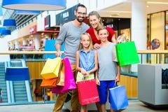 Família de quatro pessoas no shopping com sacos imagem de stock