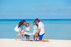 Família de quatro pessoas nova feliz com o mapa na praia imagem de stock royalty free
