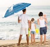 Família de quatro pessoas nova que está com dianteiro traseiro Fotografia de Stock Royalty Free