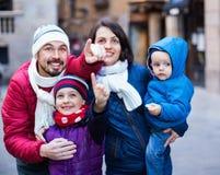 Família de quatro pessoas que anda na cidade e que olha o showplace imagem de stock royalty free