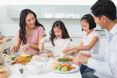 Família de quatro pessoas que aprecia a refeição saudável na cozinha Fotografia de Stock