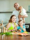 Família de quatro pessoas que cozinha a cozinha vermelha dos peixes em casa Imagens de Stock