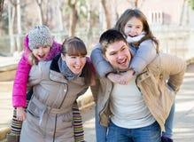 Família de quatro pessoas que levanta e que ri foto de stock