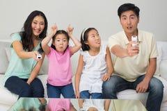 Família de quatro pessoas que olha a tevê na sala de visitas fotos de stock