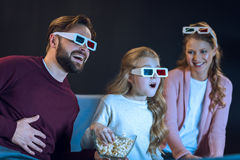 Família de riso nos vidros 3d que olha o filme e comer a pipoca Imagens de Stock