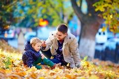 Família de riso que tem o divertimento no parque do outono Fotografia de Stock Royalty Free