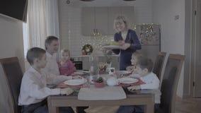A família de seis surpreendente feliz aprecia o jantar de Natal festivo no armosphere acolhedor bonito da celebração da cozinha e filme