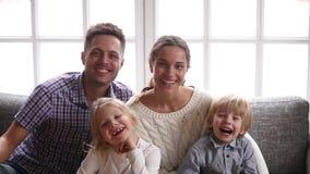 Família de sorriso alegre com as duas crianças que riem olhando a câmera filme