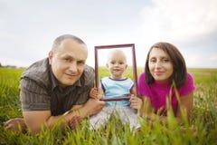Família de sorriso através do quadro Imagem de Stock