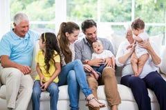 Família de sorriso com as avós que sentam-se no sofá Imagem de Stock Royalty Free