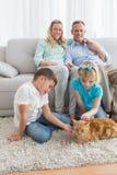 Família de sorriso com seu gato do gengibre no tapete Imagens de Stock Royalty Free