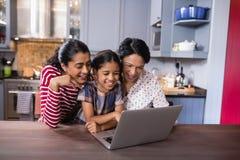 Família de sorriso da multi-geração que usa o portátil na cozinha fotografia de stock