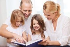 Família de sorriso e duas meninas com livro Imagens de Stock