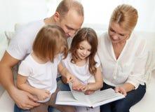 Família de sorriso e duas meninas com livro Fotografia de Stock Royalty Free