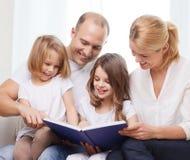 Família de sorriso e duas meninas com livro Imagem de Stock