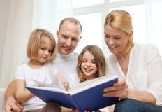 Família de sorriso e duas meninas com livro Fotografia de Stock