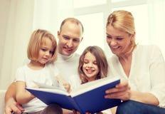 Família de sorriso e duas meninas com livro Fotos de Stock Royalty Free