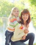 Família de sorriso feliz do retrato, criança que abraça a mãe no verão Fotografia de Stock