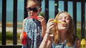 A família de sorriso feliz, irmãs é jogar, fundindo bolhas de sabão no verão exteriores Metragem conservada em estoque video estoque