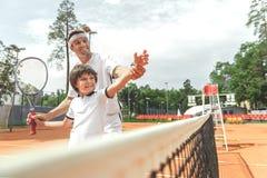 Família de sorriso feliz que joga o tênis fotos de stock royalty free