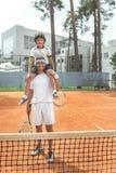Família de sorriso feliz que localiza perto da grade do tênis fotos de stock