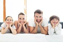 Família de sorriso na cama