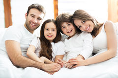 Família de sorriso na cama foto de stock