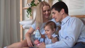 Família de sorriso na cama onde jogo do paizinho e da mamã com sua filha pequena com um brinquedo filme
