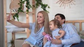 Família de sorriso na cama, onde o jogo com sua filha pequena, mamã do paizinho e da mamã toma um selfie de sua família video estoque