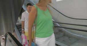 Família de sorriso na escada rolante após a compra filme