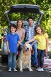 Família de sorriso na frente de um carro fotografia de stock royalty free